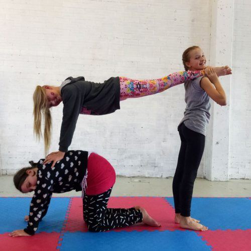 Kids working on acrobatic pyramids in Circus Akimbo youth circus class