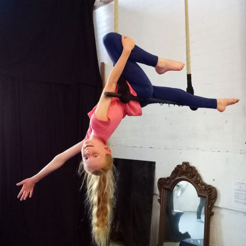 Sophia on the trapeze in a kids circus class